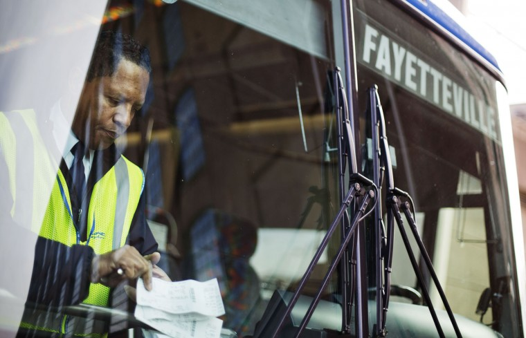 Driver Mark Green checks passenger tickets as he prepares to drive a bus to Fayetteville, N.C., ahead of the Thanksgiving holiday at a Greyhound station Tuesday, Nov. 24, 2015, in Atlanta. An estimated 46.9 million Americans are expected to take a car, plane, bus or train at least 50 miles from home over the long holiday weekend, according to the motoring organization AAA. That would be an increase of more than 300,000 people over last year, and the most travelers since 2007. (AP Photo/David Goldman)