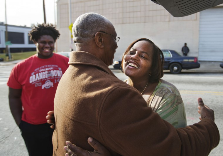 Lasaundra Dudley, of Atlanta, right, embraces her father Belvin Baldwin after he arrived off a bus from Savannah, Ga., to spend Thanksgiving with her and his grandson Vincent Buckley, left, at a Greyhound station Tuesday, Nov. 24, 2015, in Atlanta. An estimated 46.9 million Americans are expected to take a car, plane, bus or train at least 50 miles from home over the long holiday weekend, according to the motoring organization AAA. That would be an increase of more than 300,000 people over last year, and the most travelers since 2007. (AP Photo/David Goldman)