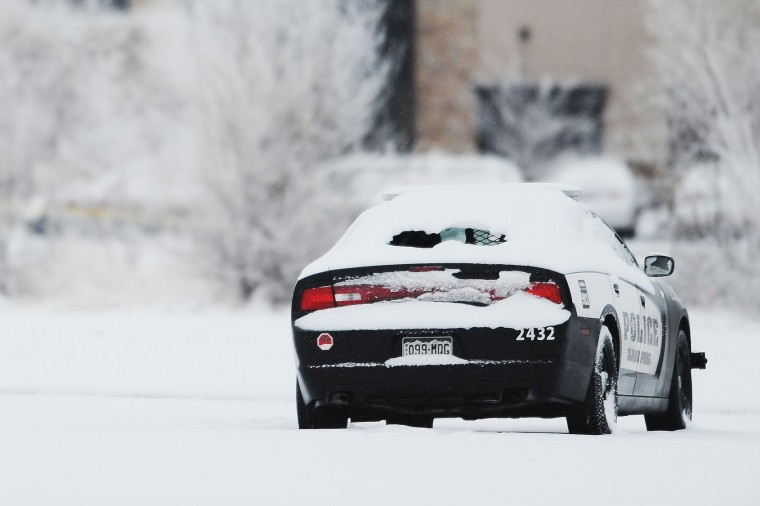 A Colorado Springs Police vehicle collects snow on its shattered back window following Friday's shooting at a Planned Parenthood clinic in Colorado Springs, Colo., Saturday, Nov. 28, 2015 . Law enforcement officers continue the investigation on Saturday, Nov. 28, 2015, following the arrest of the suspect, Robert Lewis Dear, who is now in police custody. (Daniel Owen/The Gazette via AP)