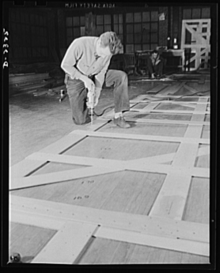 Wooden templates are used as patterns for the laying out of a number of steel plates. This worker is carrying the templates for a gun foundation from the mold loft to the plate working section. All parts are prefabricated in this huge Eastern plant which formerly turned out freight cars. The completed sections are then carried six miles to the ways on flat cars. Bethlehem-Fairfield Shipyards Inc., Baltimore, Maryland