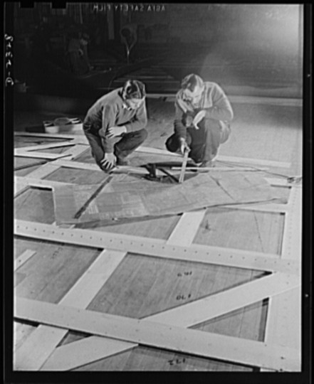 Wooden templates are used as patterns for the laying out of a number of steel plates. This worker is carrying the template for a gun foundation from the mold loft to the plate working section. All parts are prefabricated in this huge Eastern plant which formerly turned out freight cars. The completed sections are then carried six miles to the ways on flat cars. Bethlehem-Fairfield Shipyards Inc., Baltimore, Maryland