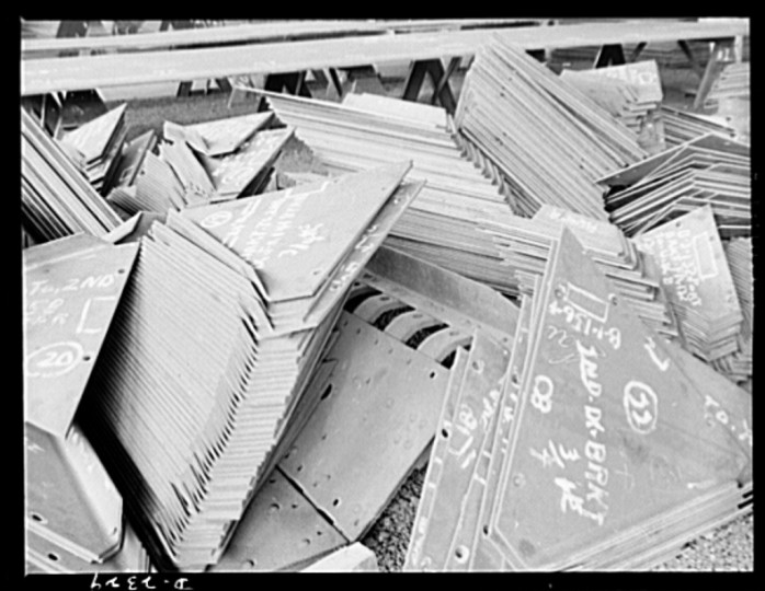 These stacks of steel plate are in readiness for an uninterrupted flow toward the production line of a large Eastern plant fabricating sections for ships built at a nearby yard. This plant was formerly used for Pullman car construction. Bethlehem-Fairfield Shipyards Inc., Baltimore, Maryland