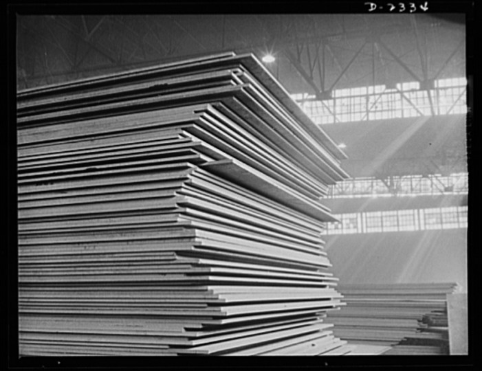 These stacks of steel plate are in readiness for an uninterrupted flow toward the production line of a large Eastern plant fabricating sections for ships built at a nearby yard. This plant was formerly used for freight car construction. All parts are prefabricated in this huge Eastern plant which formerly turned out freight cars. The completed sections are then carried six miles to the ways on flat cars. Bethlehem-Fairfield Shipyards, Inc., Baltimore, Maryland 1941