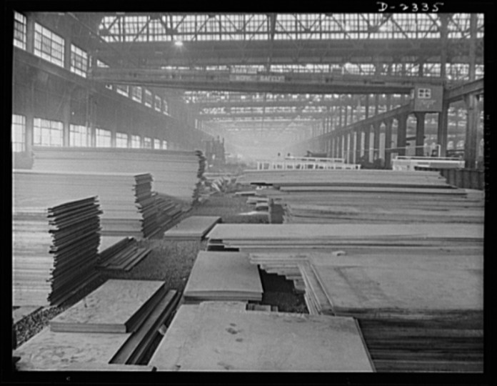 Steel plates of wasteless dimensions stacked ready for laying out, one of the first operations on the production line of multiply cargo ship construction. All parts are prefabricated in this huge Eastern plant which formerly turned out freight cars. The completed sections are then carried six miles to the ways on flat cars. Bethlehem-Fairfield Shipyards Inc., Baltimore, Maryland