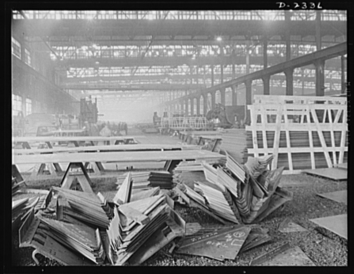 Knee brackets ready to be welded between the ship's deck beams and frames ( or ribs) at the start of the production line. All parts are prefabricated in this huge Eastern plant which formerly turned out freight cars. The completed sections are then carried six miles to the ways on flat cars. Bethlehem-Fairfield Shipyards Inc., Baltimore, Maryland
