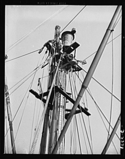 "These workers are making the final fitting and checking of the rigging of the masthead of a new member of the ""Liberty Fleet"" at a large Eastern shipyard. Bethlehem-Fairfield Shipyards Inc., Baltimore, Maryland"