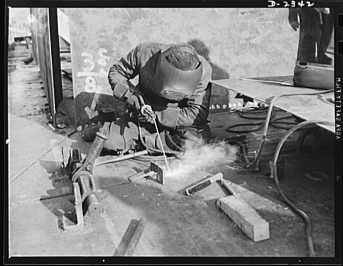 "Ratchets, turnbuckles and ""dogs"" hold these deck units of a new Liberty ship in place as a welder in a large Eastern shipyard uses the torch to fuse them"