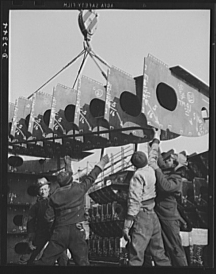 "These are prefabricated inner bottom tank sections, ready to be set in place and welded into a unit. Fabricated in an old freight car plant, they will be used in ships of the ""Liberty Fleet"" being built in a large Eastern shipyard. Bethlehem-Fairfield Shipyards Inc., Baltimore, Maryland"