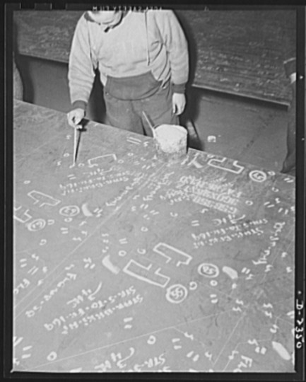 This worker in the mold loft is painting over the marks made on steel plates from wooden templates, or patterns. The original marking is scratched onto the steel, and this man brings them out in white. All parts are prefabricated in this huge Eastern plant which formerly turned out freight cars. The completed sections are then carried six miles to the ways on flat cars. Bethlehem-Fairfield Shipyards Inc., Baltimore, Maryland