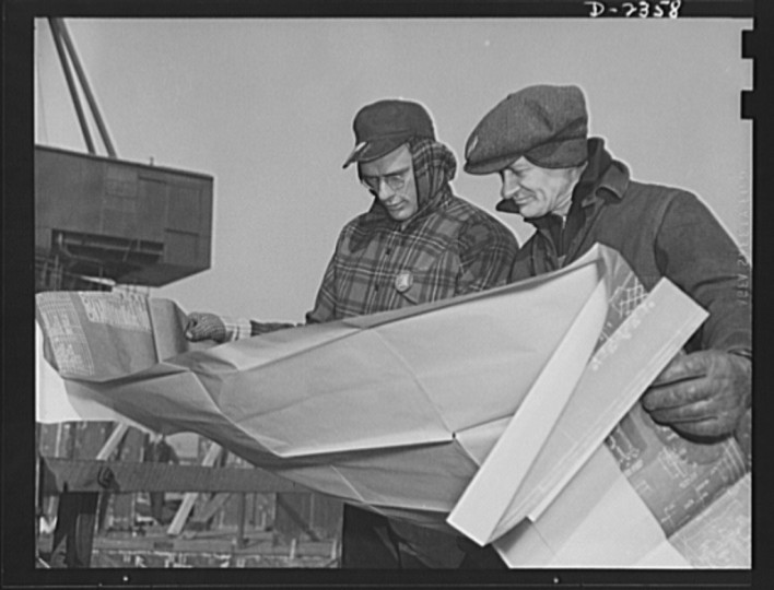 "Here a shipfitter and a crew foreman check the plans to make certain they properly locate a prefabricated section for a new ship, part of Uncle Sam's ""Liberty Fleet,"" under construction at a large Eastern yard. Bethlehem- Fairfield Shipyards Inc., Baltimore, Maryland"