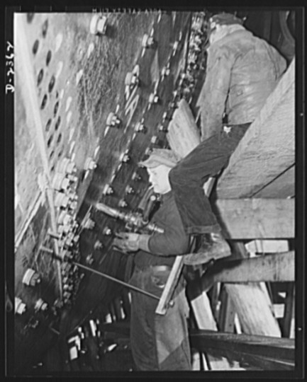 Shell plates of a ship at the bow, where the inner plates are first bolted to the outer plates for added strength. The rivets are countersunk to be flush on the outer side. Production scene in a large Eastern shipyard. Bethlehem-Fairfield Shipyards Inc., Baltimore, Maryland