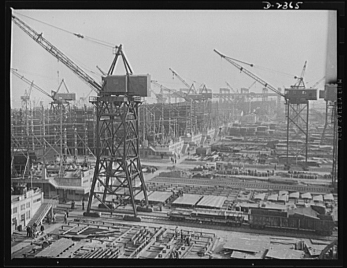 This maze of rolling cranes, at a large Eastern shipyard is a typical scene in many large shipyards at work on ships for Uncle Sam's Navy and merchant fleet. Stocks of material are piled up for the cranes to take to vessels under construction so there is no delay in production while waiting for sections or materials. All parts are prefabricated in this Eastern plant which formerly turned out freight cars. The completed sections are then carried six miles to the ways on flat cars. Bethlehem-Fairfield Shipyards Inc., Baltimore, Maryland