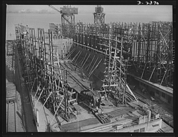 A new vessel has just moved off these ways, and the keel is being assembled for yet another in a large Eastern shipyard. The bottom and side shell plating and the inner tank sections are being assembled. All parts are prefabricated in this huge Eastern plant which formerly turned out freight cars. The completed sections are then carried six miles to the ways on flat cars