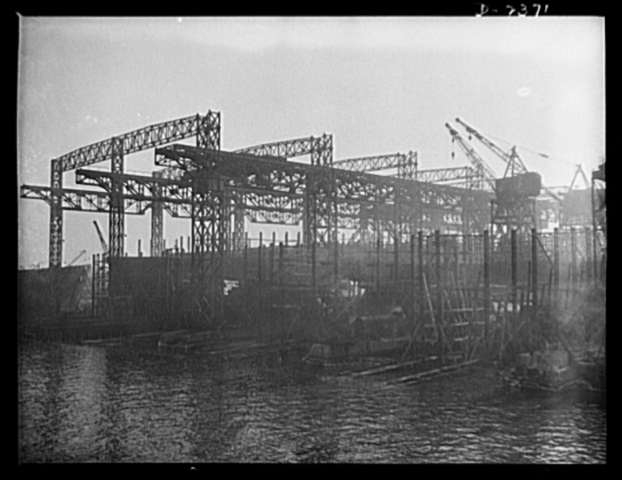 A view from the water of the shipways at a large Eastern yard. At the left is seen the old-style superstructure, with tracks for two-way overhead cranes, while at the right, running on ground tracks, are the more modern cranes, designed for hoisting from any angle. Bethlehem-Fairfield Shipyards Inc., Baltimore, Maryland