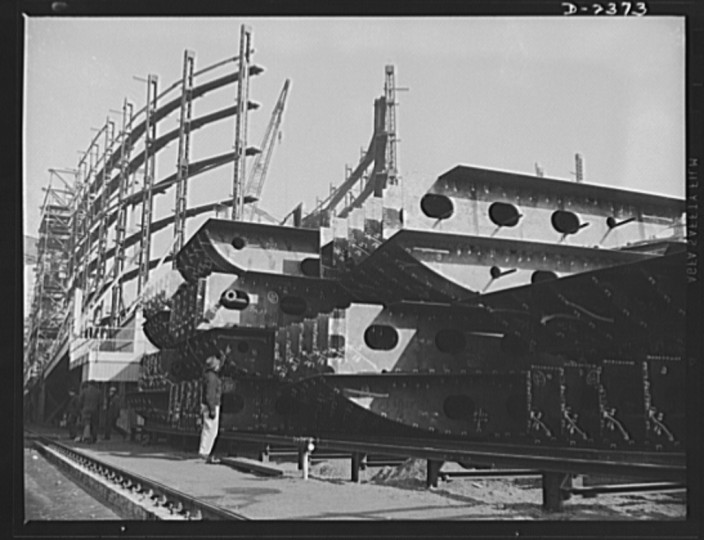 This is the midship section of a new member of the Liberty Fleet, nearing completion at a large Eastern shipyard. In the background is a maze of scaffolding and cranes typical of the scene in many large American shipyards as builders work to make Uncle Sam master of the seas