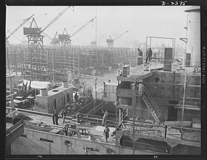 This is the midship section of a new member of the Liberty Fleet, nearing completion at a large shipyard. In the background is a maze of scaffolding and cranes typical of the scene in many large American shipyards as builders work to make Uncle Sam master of the seas