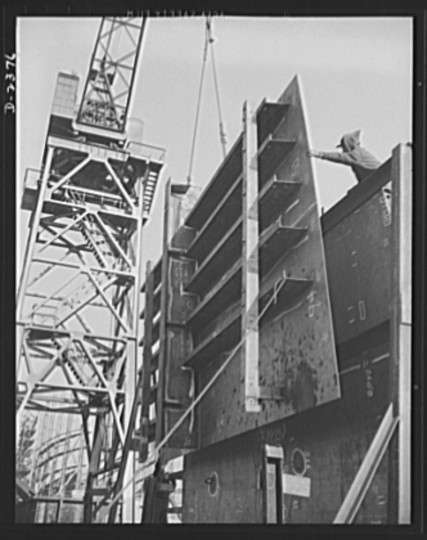 All assembled and ready to go in place. Prefabrication of sections such as this in a nearby plant formerly making freight cars saves weeks in the building of ships for Uncle Sam's new merchant fleet. This piece is being hoisted into place, and soon the welder will begin his vital work. Bethlehem-Fairfield Shipyards Inc., Baltimore, Maryland