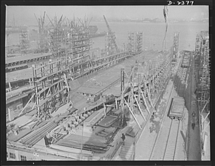 A new vessel has just moved off these ways, and the keel is being assembled for yet another, in a large Eastern yard. The bottom and side shell plating and the inner tank sections are being assembled. Another new keel has been laid on the ways to the left. All parts are prefabricated in this huge Eastern plant which formerly turned out freight cars. The completed sections are then carried six miles to the ways on flat cars