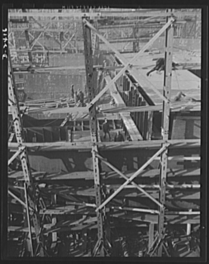 This is the midship section of a new member of the Liberty Fleet, nearing completion at a large Eastern shipyard. In the background is a maze of scaffolding and cranes typical of the scene in many large American shipyards as builders work to make Uncle Sam master of the seas. Bethlehem-Fairfield Shipyards Inc., Baltimore, Maryland