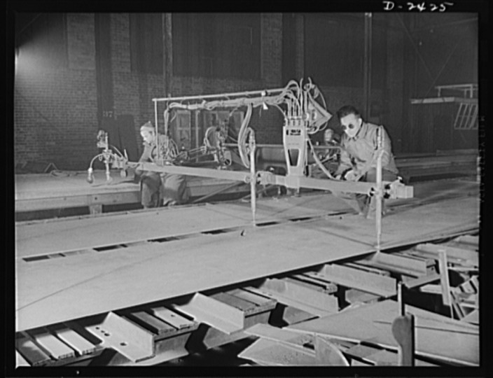 "This is a travograph-oxy-acetylene machine, a cutter which treads its own pattern. Here it is cutting two identical floor plates for a tank section at the bottom of a new member of the ""Liberty Fleet."" The work is done at what was formerly a freight car plant now a large Eastern plant. All parts are prefabricated in this huge Eastern plant which formerly turned out freight cars. The completed sections are then carried six miles to the ways on flatcars. Bethlehem-Fairfield Shipyards Inc., Baltimore, Maryland"