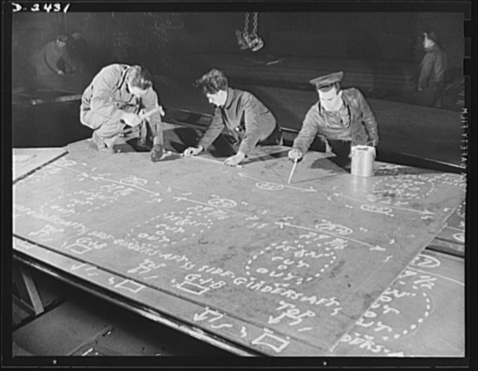 This worker in the mold loft is painting over the marks made on steel plates from wooden templates, or patterns. The original marking is scratched onto the steel, and this man brings them out in white. All parts are prefabricated in this huge Eastern plant which turned out freight cars. The completed sections are then carried six miles to the ways on flatcars. Bethlehem-Fairfield Shipyards Inc., Baltimore, Maryland