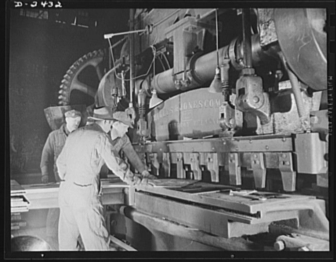 "Workers at a prefabricating plant turn out steel parts for a large Eastern shipyard building units of Uncle Sam's ""Liberty Fleet."" Here they operate a giant shear. This plant was originally used to produce freight cars, and the shears are part of the plant's original equipment. All parts are prefabricated in this huge Eastern plant which formerly turned out freight cars. The completed sections are then carried six miles to the ways on flatcars. Bethlehem-Fairfield Shipyards Inc., Baltimore, Maryland"