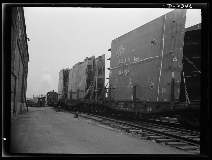 These flat cars loaded with prefabricated and assembled sections for ships under construction at a large Eastern yard are leaving nearby plant formerly used for the manufacture of Pullman cars. The work of this plant means many valuable months saved in building of Uncle Sam's Liberty Fleet. All parts are prefabricated in this huge Eastern plant which formerly turned out freight cars. The completed sections are then carried six miles to the ways on flat cars. Bethlehem- Fairfield Shipyards Inc., Baltimore, Maryland