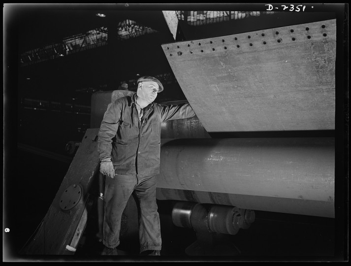 This worker is watching for signals from a colleague as he rolls cold steel plate to a desired shape on this plate roller, designed in Germany. All parts are prefabricated in this Eastern plant which formerly turned out freight cars. The completed sections are carried to the ways on flat cars. Bethlehem-Fairfield Shipyards Inc., Baltimore, Maryland