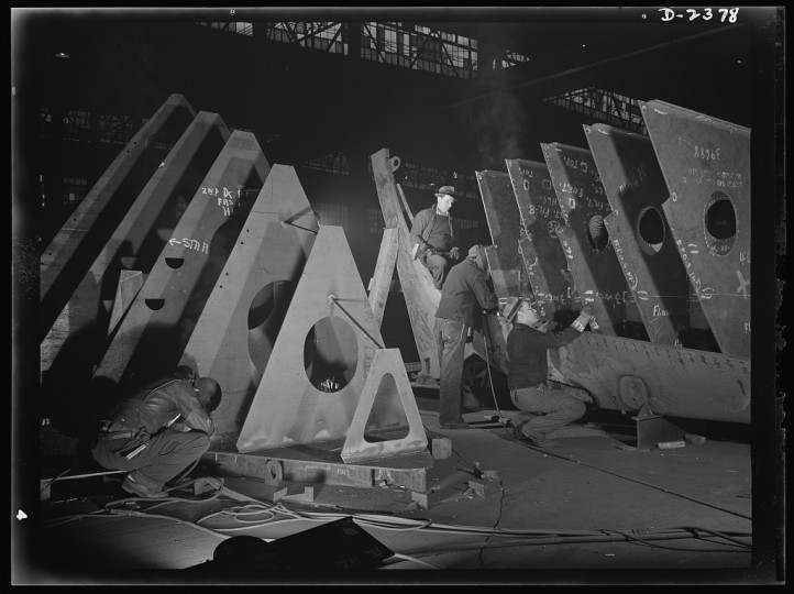 In an abandoned freight car factory near the Atlantic coast, sections of sleek freighters for the merchant fleet are being prefabricated. Present rate of production is one a week. The men shown at work here believe they can increase that rate to one in six days
