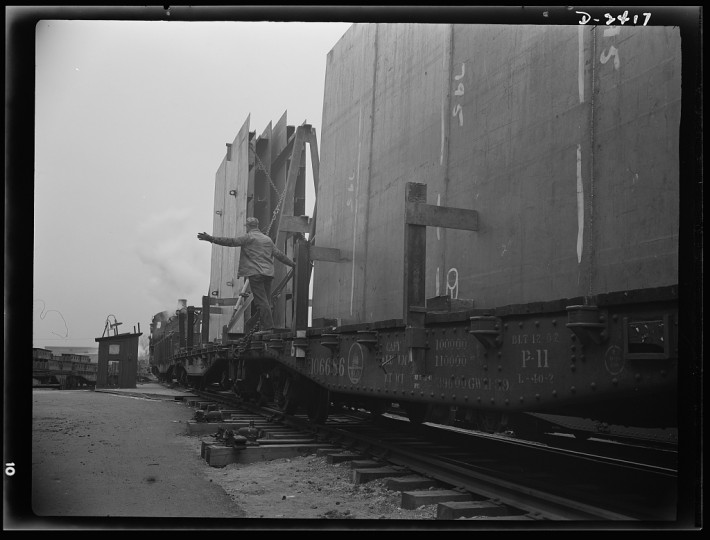 "These flatcars loaded with prefabricated and assembled sections for ships under construction at a large Eastern yard are leaving a nearby plant formerly used for the manufacture of Pullman cars. The work of this plant means many valuable months saved in the building of Uncle Sam's ""Liberty Fleet."" All parts are prefabricated in this huge Eastern plant which formerly turned out freight cars. The completed sections are then carried six miles to the ways on flatcars. Bethlehem-Fairfield Shipyards Inc., Baltimore, Maryland"