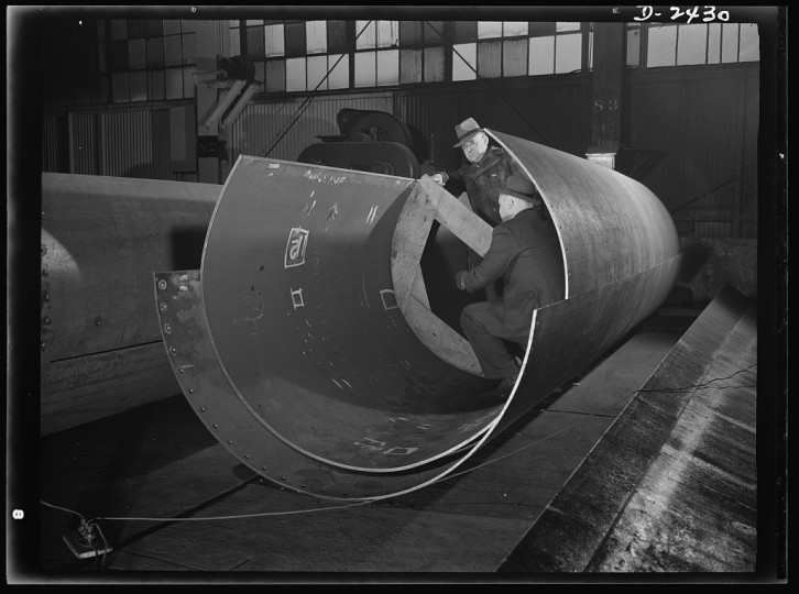 "These are rolled plates for the shaft tunnel of one of Uncle Sam's new ""Liberty Ships,"" under construction at a large Eastern shipyard. All parts are prefabricated in this large Eastern plant which formerly turned out freight cars. The completed sections are then carried six miles to the ways on flatcars. Bethlehem-Fairfield Shipyards Inc., Baltimore, Maryland"