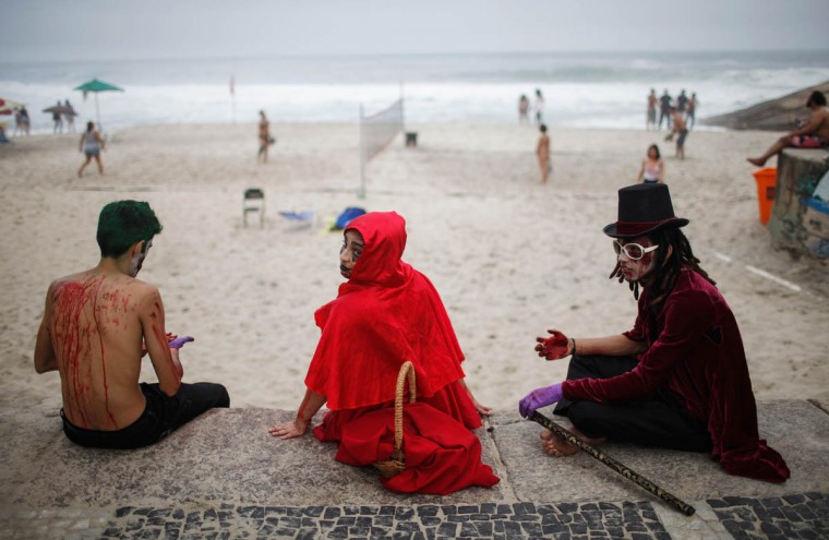 Revelers sit along Diabo beach during Day of the Dead festivities on November 2, 2015 in Rio de Janeiro, Brazil. Brazilians often mark the traditional Mexican holiday by visiting loved ones' graves and sometimes leaving offerings of food or drink. Many revelers came to the area during a 'Zombie Walk'. (Mario Tama/Getty Images)