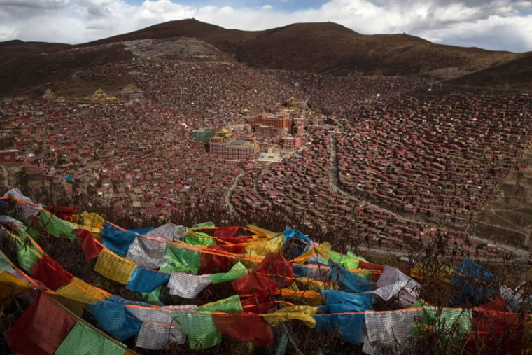 Tibetan prayer flags, known as Lung-ta, flutter on a hillside above the Larung Wuming Buddhist Institute on Friday in the Larung Valley of Sertar county, in the remote Garze Tibetan Autonomous Prefecture, Sichuan province, China. Located high in the mountains of Sichuan, the Larung Wuming Buddhist Institute was founded in 1980 by an influential lama of the Nyingma sect and is widely regarded as the world's largest and most influential centre for Tibetan Buddhist studies. The school is home to thousands of monks and nuns and is popular for followers from all over the Tibetan areas and other parts of China.  (Kevin Frayer/Getty Images)