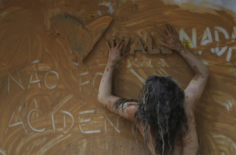 A protester washes muddy water over the Vale logo at the entrance to Vale headquarters on November 16, 2015 in Rio de Janeiro, Brazil. The bursting of two dams at the Samarco mining operation, jointly owned by Vale and BHP Billiton, unleashed a flood of muddy waste which mostly leveled a village in Minas Gerais state. The massive mudflow left ten people dead and an environmental aftermath polluting downstream waters. (Photo by Mario Tama/Getty Images)