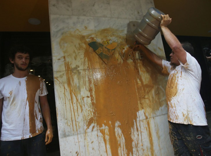 A protester splashed muddy water over the Vale logo at the entrance to Vale headquarters on November 16, 2015 in Rio de Janeiro, Brazil. The bursting of two dams at the Samarco mining operation, jointly owned by Vale and BHP Billiton, unleashed a flood of muddy waste which mostly leveled a village in Minas Gerais state. The massive mudflow left ten people dead and an environmental aftermath polluting downstream waters. (Photo by Mario Tama/Getty Images)