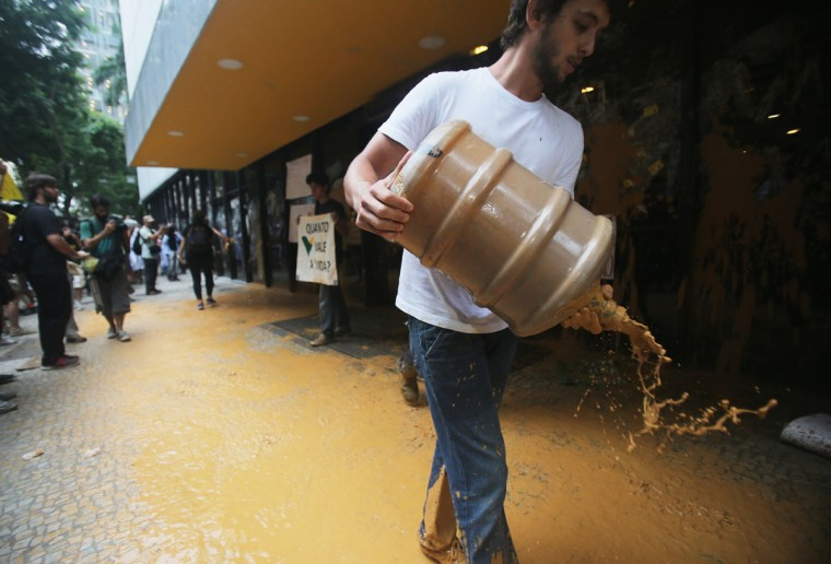 A protester splashes muddy water at the entrance to Vale headquarters on November 16, 2015 in Rio de Janeiro, Brazil. (Photo by Mario Tama/Getty Images)