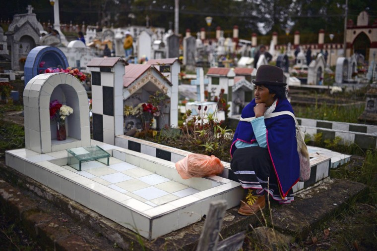 "A Colombian indigenous woman of the Misak ethnic group sits by the grave of a relative at the cemetery in Silvia, department of Cauca, Colombia, on November 1, 2015, during the celebration of All Saints Day. The Misaks are, of the hundred indigenous groups that inhabit Colombia, the ones who have their customs best preserved, including a colorful ceremony of offerings to the dead, closely related to the cult of ""Mother Earth"" and the New Year. The Day of the Offerings is celebrated between November 1 and 2, when the favorite food of the dead is prepared to receive their spirits and harmonize the territory. (Luis Robayo/Getty Images)"