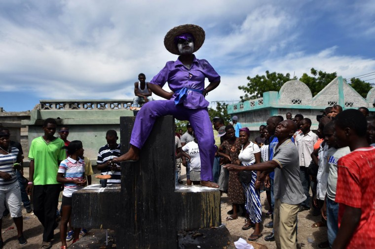 A woman devotee in the role of a spirit known as a Gede is seen during ceremonies honoring the Haitian voodoo spirits of Baron Samdi and Gede on the Day of the Dead in the National Cemetery in Port-au-Prince, Haiti on November 2, 2015. Revelers streamed into cemeteries across Haiti bearing beeswax candles, food offerings and bottles of rum infused with hot peppers to mark the country's annual Voodoo festival of the dead. (Hector Retamal/Getty Images)
