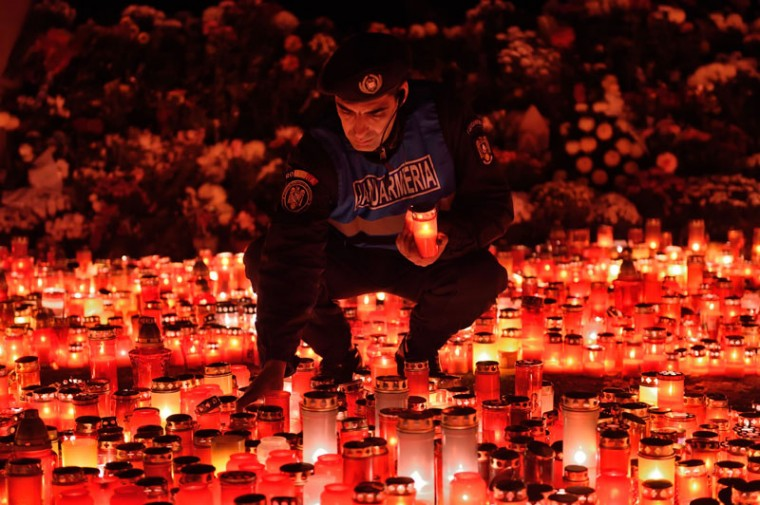 "A Romanian gendarme places candles given by the people who came to pay respect for the victims of the fire at the ""Colectiv"" nightclub in Bucharest, on Monday. A fire and stampede at the club during on Saturday left 31 people dead and nearly 200 injured. (DANIEL MIHAILESCU/AFP/Getty Images)"