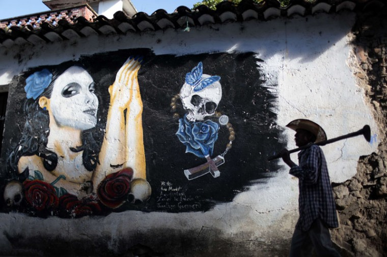 A man walks next to a mural in Tixtla, Guerrero State, Mexico, during the celebration of All Souls Day on Monday. (Pedro PARDO/AFP/Getty Images)