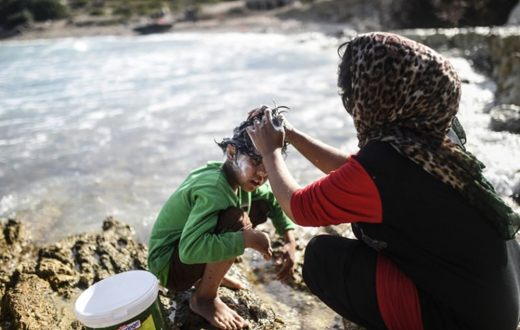 A woman washes her child's hair as they wait along with other migrants and refugees to travel to the Greek island of Chios from Cesme in the Turkish province of Izmir on Tuesday. Amnesty International criticized Europe's failure to stop migrant deaths in the Aegean Sea as the death toll from ramshackle boats sinking off Greece rises daily. The group said over 450 refugees and migrants had died or gone missing in successive Aegean Sea sinkings in the first 10 months of the year. (BULENT KILIC/AFP/Getty Images)