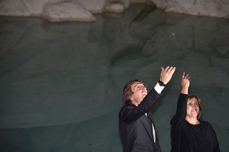Fendi's Ceo, Pietro Beccari (left) and Silvia Venturini Fendi throw coins into the restored Trevi fountain during its inauguration on November 3, 2015 in central Rome. (ALBERTO PIZZOLI/AFP/Getty Images)