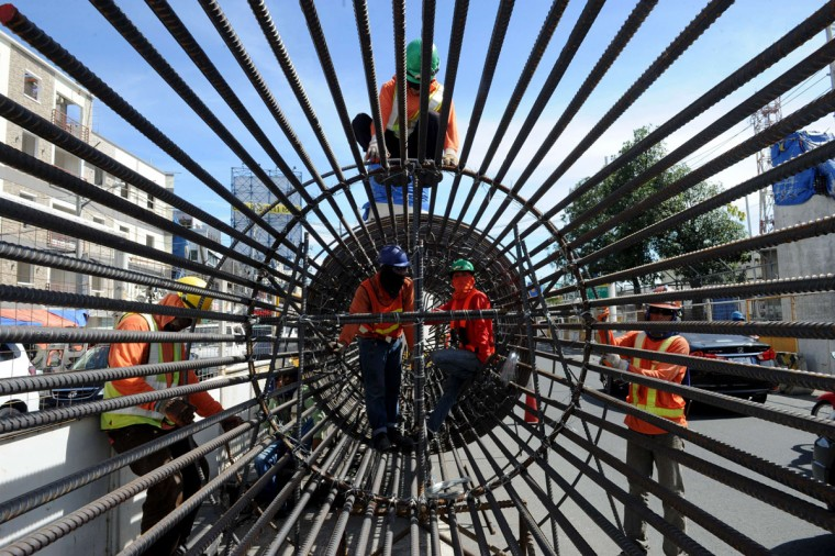 Construction workers prepare to put up a column for an elevated highway project in Manila on November 4, 2015. The government is rushing the construction of toll roads to solve a worsening traffic situation. (AFP Photo/Jay Directo)