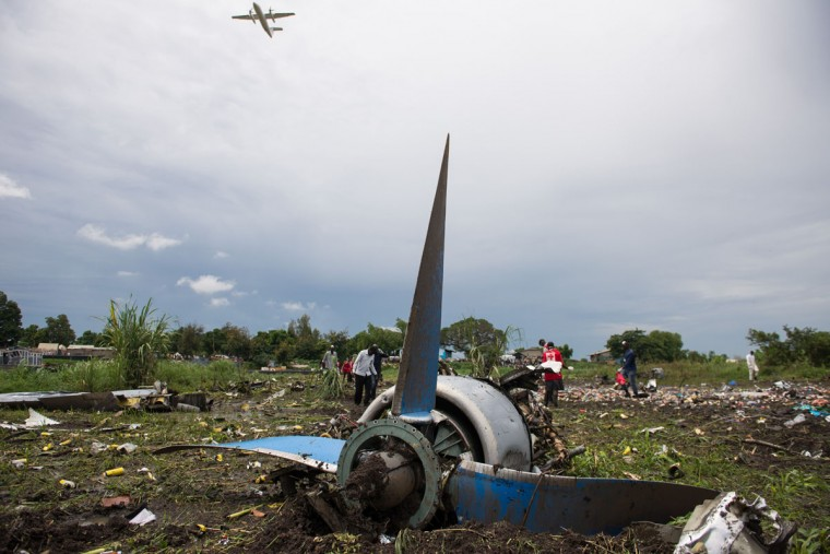 People gather at the site of a cargo plane crash, on a small island in the White Nile river, close to Juba airport, in the Hai Gabat residential area, on November 4, 2015. At least 27 people were killed today when a plane crashed shortly after taking off from South Sudan's capital Juba, an AFP reporter said. Police were pulling the bodies of men, women and children out of the wreckage of the Russian-built Antonov An-12 cargo plane, which smashed into a farming community on an island on the White Nile river, according to the reporter, who counted at least 27 dead. (AFP Photo/Charles Lomodong)