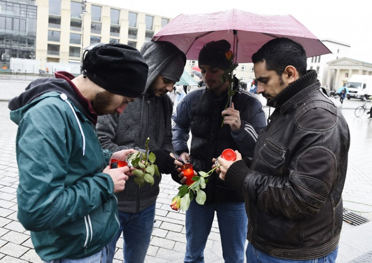 Syrian refugees light candles to place them outside the French embassy to Germany in Berlin on Sunday for victims of the Friday attacks in Paris. Syrian activist Monis Bukhari called out for a gathering of Syrians at the French embassy. German Interior Minister Thomas de Maiziere made a plea against linking the terror attacks in Paris to the record influx of asylum seekers into Europe. (TOBIAS SCHWARZ/AFP/Getty Images )