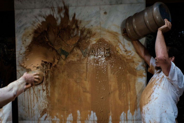 People throw muddy water on the façade of Brazilian mining company Vale headquarters during a protest in Rio de Janeiro, Brazil, on November 16, 2015. The bursting of two dams at a mine operated by Brazilian company Samarco - equally owned by Vale and Australian BHP Billiton- unleashed torrents of waste that flattened a village in Minas Gerais State on November 5 killing ten people. Brazilian mining firm Samarco promised Monday to pay at least $260 million for damage from the bursting, prosecutors said. (YASUYOSHI CHIBA/AFP/Getty Images)