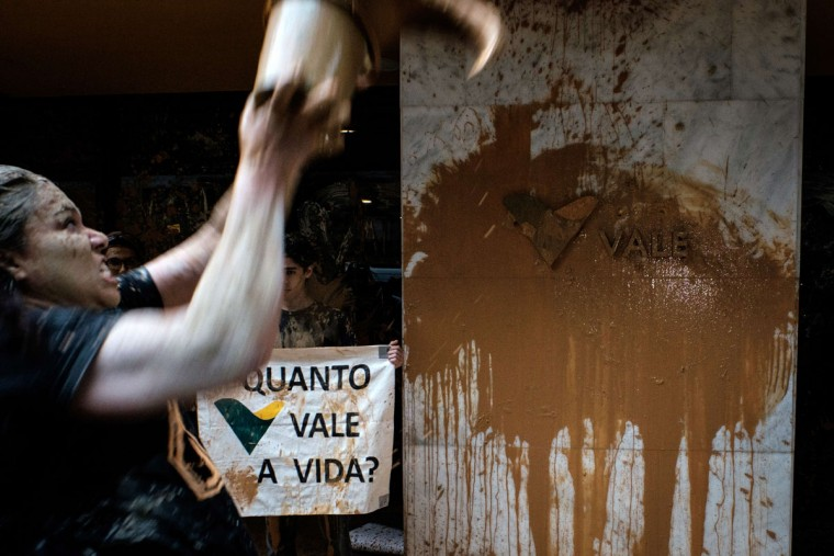 """A woman throws muddy water on the façade of Brazilian mining company Vale headquarters next to a sign reading """"How much does a life cost?"""" during a protest in Rio de Janeiro, Brazil, on November 16, 2015. The bursting of two dams at a mine operated by Brazilian company Samarco - equally owned by Vale and Australian BHP Billiton- unleashed torrents of waste that flattened a village in Minas Gerais State on November 5 killing ten people. Brazilian mining firm Samarco promised Monday to pay at least $260 million for damage from the bursting, prosecutors said. (YASUYOSHI CHIBA/AFP/Getty Images)"""