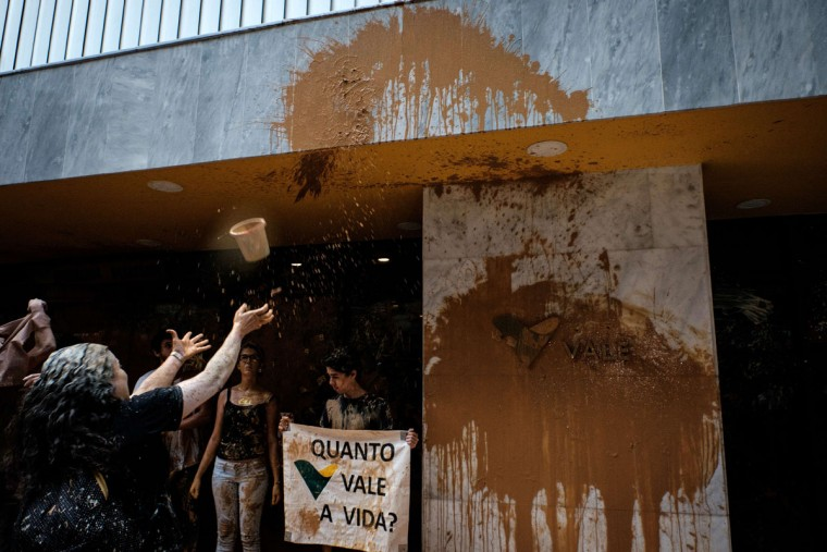 """A protester throws muddy water on the façade of Brazilian mining company Vale headquarters as another holds a sign reading """"How much does a life cost?"""" in Rio de Janeiro, Brazil, on November 16, 2015. The bursting of two dams at a mine operated by Brazilian company Samarco - equally owned by Vale and Australian BHP Billiton- unleashed torrents of waste that flattened a village in Minas Gerais State on November 5 killing ten people. Brazilian mining firm Samarco promised Monday to pay at least $260 million for damage from the bursting, prosecutors said. (YASUYOSHI CHIBA/AFP/Getty Images)"""