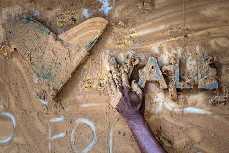 A protester spreads muddy water on the façade of Brazilian mining company Vale headquarters in Rio de Janeiro, Brazil, on November 16, 2015. The bursting of two dams at a mine operated by Brazilian company Samarco - equally owned by Vale and Australian BHP Billiton- unleashed torrents of waste that flattened a village in Minas Gerais State on November 5 killing ten people. Brazilian mining firm Samarco promised Monday to pay at least $260 million for damage from the bursting, prosecutors said. (YASUYOSHI CHIBA/AFP/Getty Images)