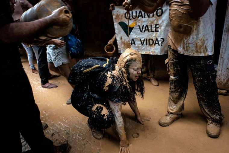 """Protesters throw muddy water on the façade of Brazilian mining company Vale headquarters next to a sign reading """"How much does a life cost?"""" in Rio de Janeiro, Brazil, on November 16, 2015. The bursting of two dams at a mine operated by Brazilian company Samarco - equally owned by Vale and Australian BHP Billiton- unleashed torrents of waste that flattened a village in Minas Gerais State on November 5 killing ten people. Brazilian mining firm Samarco promised Monday to pay at least $260 million for damage from the bursting, prosecutors said. (YASUYOSHI CHIBA/AFP/Getty Images)"""